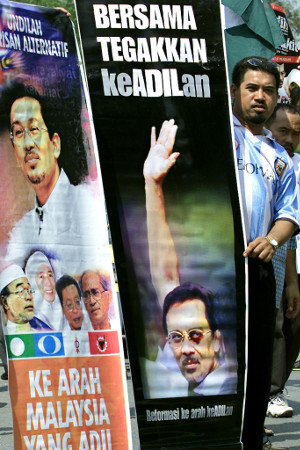 A supporter of Anwar Ibrahim holds a banner depicting Anwar's black eye during a peaceful demonstration to mark the opposition leader's 54th birthday, in Sungai Buloh, Malaysia, Aug. 12, 2001. [AFP]