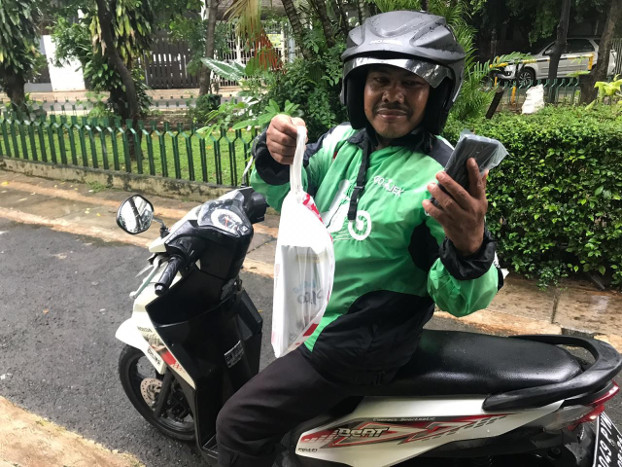 Joni Yanto, an app-based motorcycle taxi driver, shows food he is about to deliver in Jakarta, March 20, 2020. [Ronna Nirmala/BenarNews]