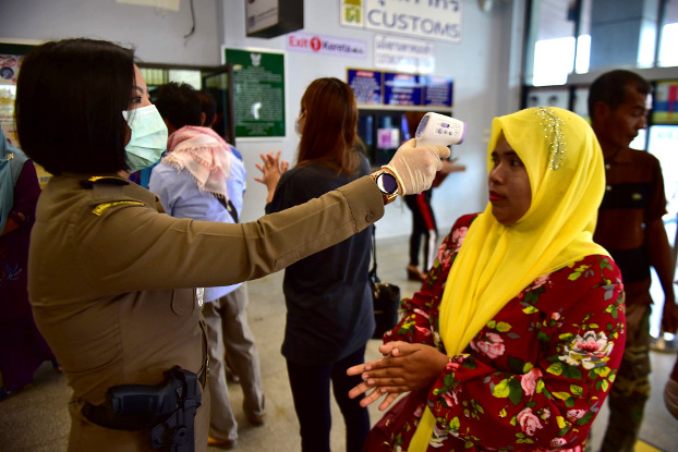 A Thai immigration officer checks the body temperature of a traveler returning from Malaysia at a border checkpoint in Narathiwat province, March 16, 2020. [Matahari Ismail/BenarNews]