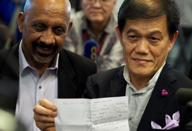 Malaysian defense attorney Hisyam Teh Poh Teik (right), flanked by colleague Narin Singh at the Kuala Lumpur International Airport, shows a letter of thanks that Vietnamese client Doan Thi Huong wrote prior to her release from prison, May 3, 2019. [Hadi Azmi/BenarNews]