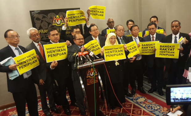 "Opposition coalition members hold signs saying ""Rise Up, People, and Stop the Fraud"" at a press conference after parliament approved electoral redistricting, March 28, 2018. [Fadzil Aziz/BenarNews]"