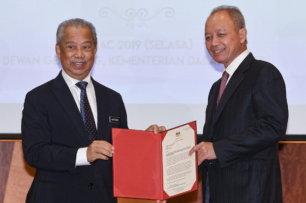 Home Minister Muhyiddin Yassin (left) presents a Royal Commission of Inquiry appointment letter to former Chief Justice Arifin Zakaria in Putrajaya, Malaysia. March 5, 2019. [S. Mahfuz/BenarNews]