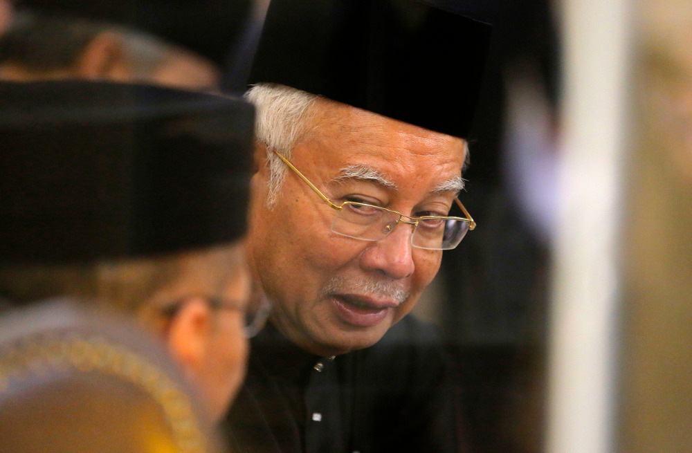 Former Prime Minister Najib Razak talks to a member of the Malaysian parliament