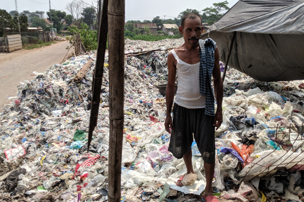 A man stands on tons of imported plastic trash at a dumpsite in Bekasi, a city in West Java, Indonesia, May 16, 2018. [Ahmad Syamsudin/BenarNews]