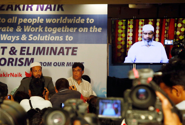Indian journalists ask questions to Islamic preacher Zakir Naik (right) during a video conference in Mumbai, India, July 15, 2016. [AP]