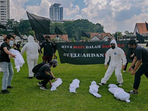 """Activists place dummy corpses of COVID-19 victims in front of a Malay banner that says """"We Die in Rebellion,"""" and """"Come Out and Fight,"""" as they call for Prime Minister Muhyiddin Yassin's resignation over his perceived failure to stem the pandemic."""
