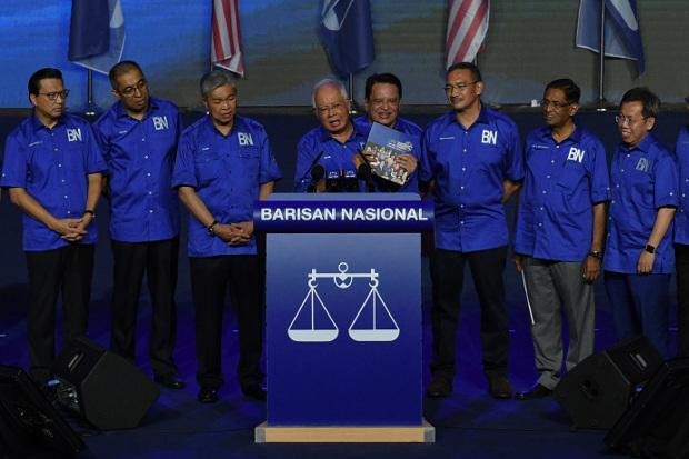 Malaysian Prime Minister Najib Razak holds a copy of his party's campaign manifesto in Kuala Lumpur, April 7, 2018. [S.Mahfuz/BenarNews]
