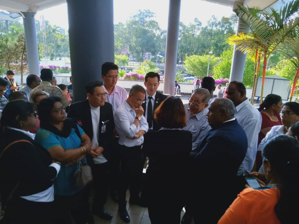 Democratic Action Party leader Lim Kit Siang (checkered shirt) talks to other DAP members at the Malacca Sessions Court, Oct. 29, 2019. [Courtesy of Royal Malaysia Police]