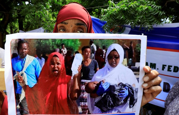 Somali women hold a photograph of a child injured in a car bomb explosion at the Afgoye junction, as they participate in a protest against the al-Shabaab militant group outside the General Kahiye Police Academy in Mogadishu, Jan. 2, 2020.