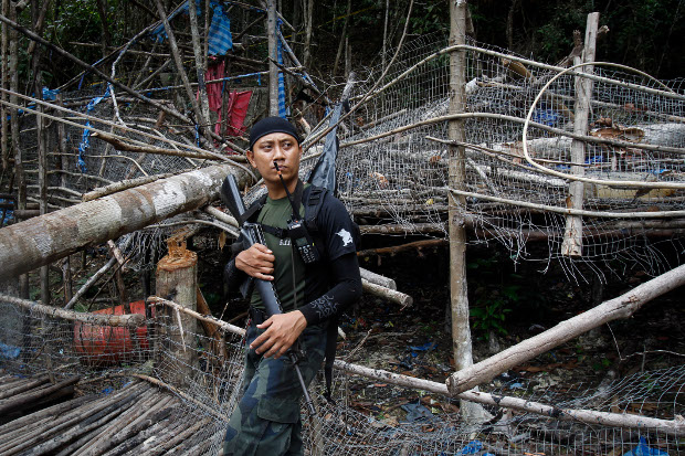 A member of the Malaysian General Operation Force stands guard at an abandoned human-trafficking camp found outside Wang Kelian in Malaysia, May 26, 2015. [AP]