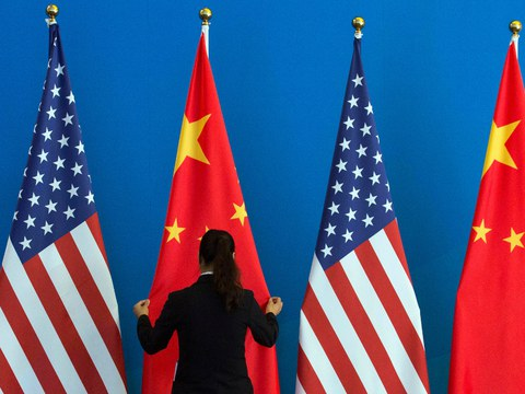 A Chinese government staff member adjusts U.S. and Chinese national flags after a strategic meeting between officials of the two countries, Beijing, July 10, 2014.