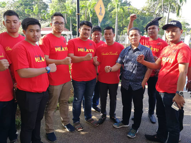 UMNO youth leader Noor Hariri Mohd Noor (in blue) poses with a group of men from Kelantan state who arrived at the court complex at 5:30 a.m. to show support for the former prime minister. [N. Nantha/BenarNews]