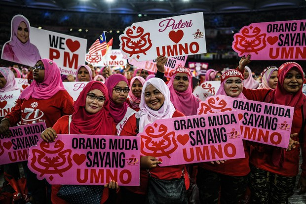 Supporters of the United Malays National Organization hold signs during the party's 71st anniversary celebration at Bukit Jalil stadium in Kuala Lumpur, May 11, 2017.
