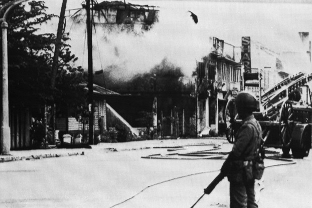A Malaysian soldier stands guard as a fire brigade battles a blaze in some shops and homes in Kuala Lumpur, May 17, 1969. (AP)
