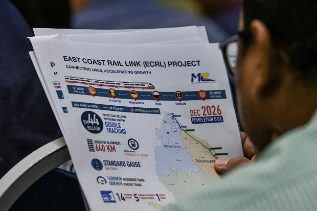 A journalist reads a handout on the East Coast Rail Link project distributed at a press conference in Putrajaya, Malaysia. April 15, 2019. [S. Mahfuz/BenarNews]