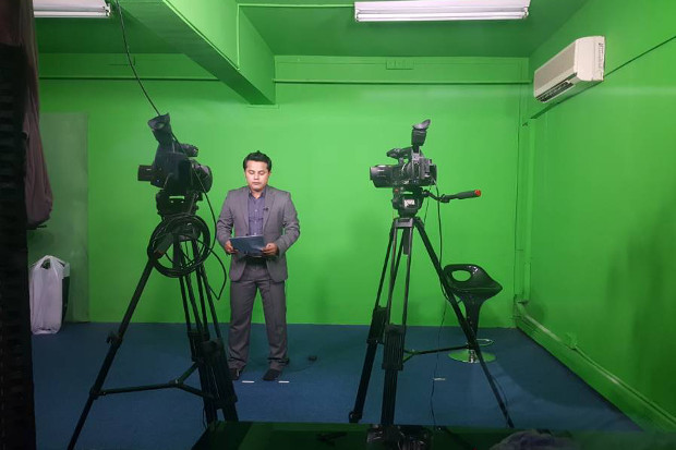 Presenter and journalist Ajmeer Omar records a stand-up report at the Rohingya Vision TV studio in Ampang, Kuala Lumpur. [Courtesy of Rohingya Vision TV]