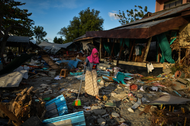 A woman clears debris from her house in Palu, in Indonesia's Central Sulawesi province, in the aftermath of a devastating earthquake and tsunami last month, on Oct. 8, 2018. [AFP]