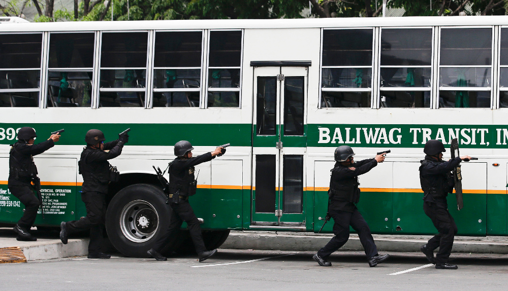 Police aim their pistols toward a bus during a hostage-taking scenario as part of anti-terrorism drills conducted by police and military units in Manila, April 12, 2018.