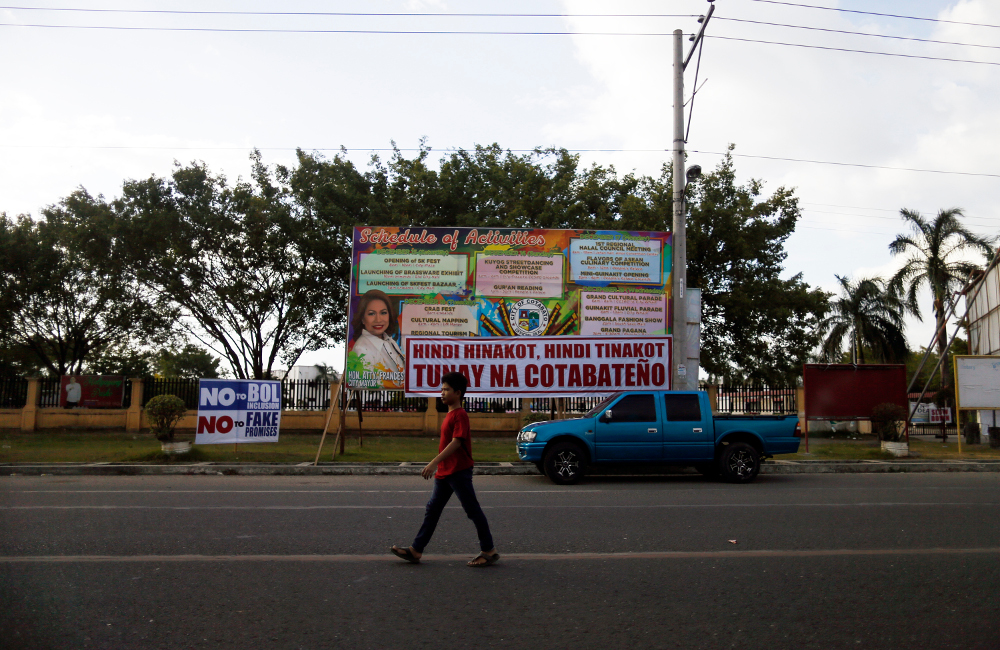 A resident crosses a street in Cotabato City, southern Philippines, ahead of a Jan. 21 plebiscite on ratifying the Bangsamoro Organic Law (BOL), which would give former Muslim rebels full control over an autonomous homeland in the region, Jan. 13, 2019. [Jeoffrey Maitem/BenarNews]