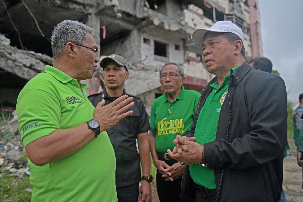 Murad Ebrahim (right), chairman of the Moro Islamic Liberation Front, talks to supporters while campaigning for the Bangsamoro Organic Law on regional autonomy, in the battle-ravaged southern Philippine city of Marawi, Dec. 22, 2018. [Froilan Gallardo/BenarNews]