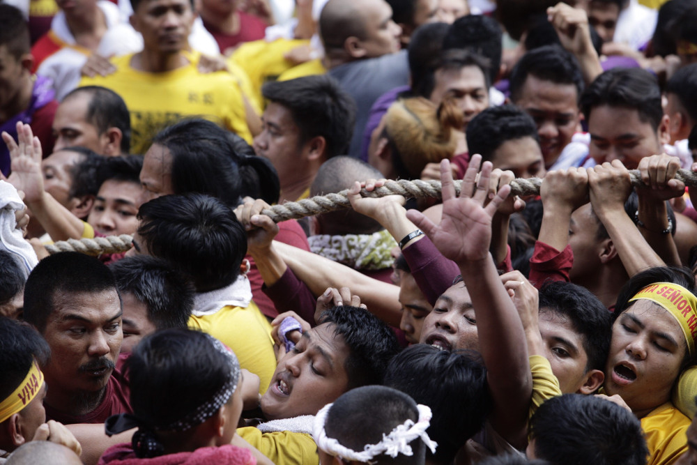 Filipinos shove one another as they try to get close the statue of the Black Nazarene during its procession in Manila, Jan. 9, 2019. [Luis Liwanag/BenarNews]