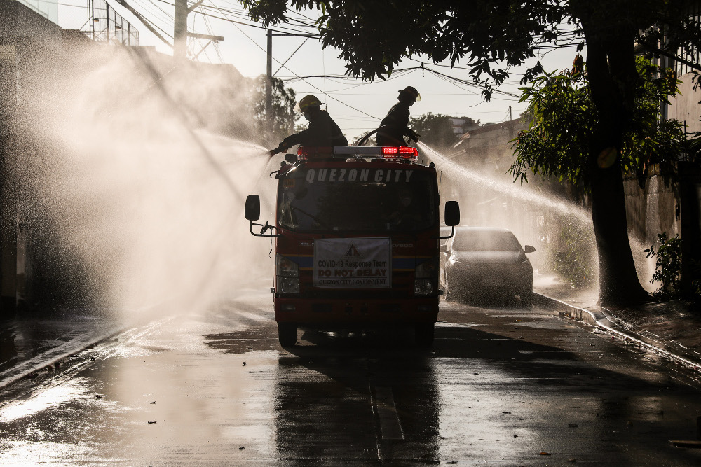 Government emergency workers spray disinfectant solution on the street in suburban Quezon City, north of Manila, March 28, 2020. [Basilio Sepe/BenarNews]