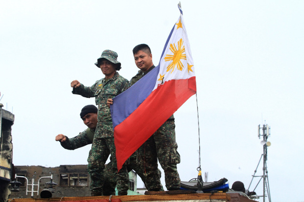 """Philippine soldiers celebrate in Marawi after President Rodrigo Duterte declared the """"liberation"""" of the southern city from Islamic State-linked militants, Oct. 17, 2017."""