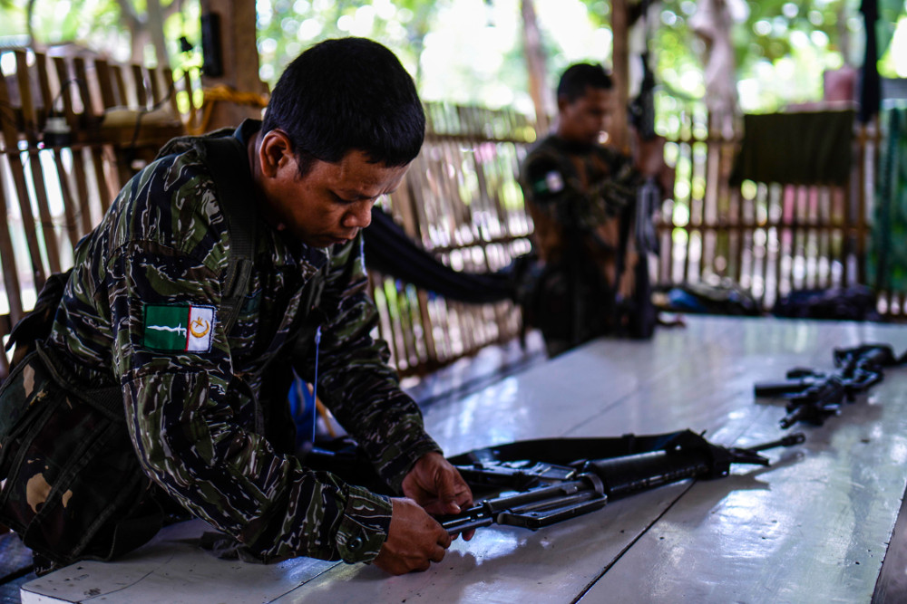 Moro Islamic Liberation Front fighters clean their rifles inside a security checkpoint at Camp Darapanan in Sultan Kudarat, a town in Maguindanao province, southern Philippines, June 22, 2019. (Photo: Jojo Rinoza/BenarNews)