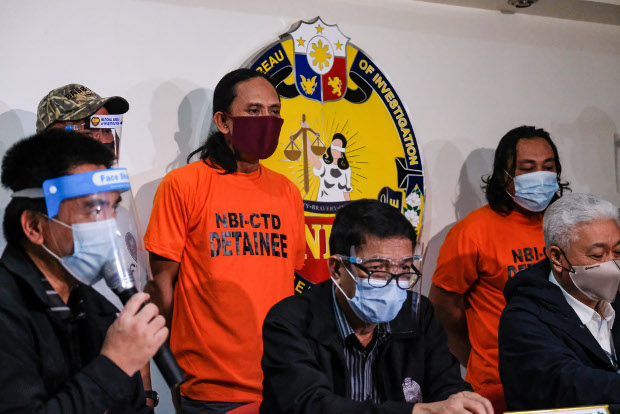 Officials with the National Bureau of Investigation announce the arrests of two suspected members of the Abu Sayyaf Group, identified as Jamar Ibi, also known as Bas, and Raden Jamil, also known as Tamiya, (standing and wearing orange shirts), at a press conference in Manila, Oct. 20, 2020. [Stringer/BenarNews]