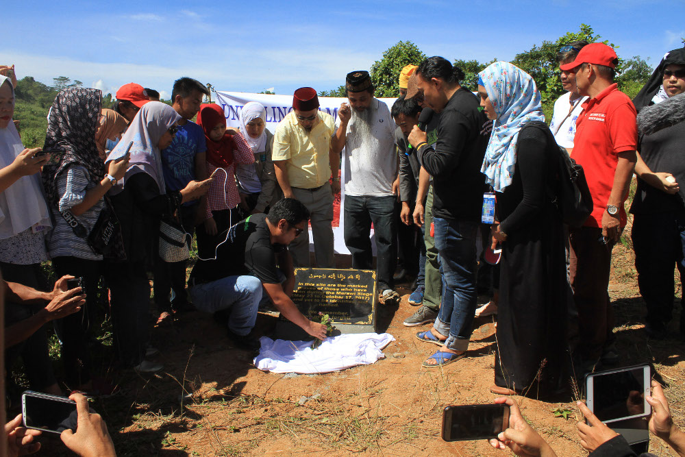 Residents of Marawi unveil a memorial plaque at the site of a mass grave holding the bodies of 281 unidentified people, who died during a five-month takeover of the city by militants and a battle with government forces that ensued, May 23, 2019. [Richel V. Umel/BenarNews]