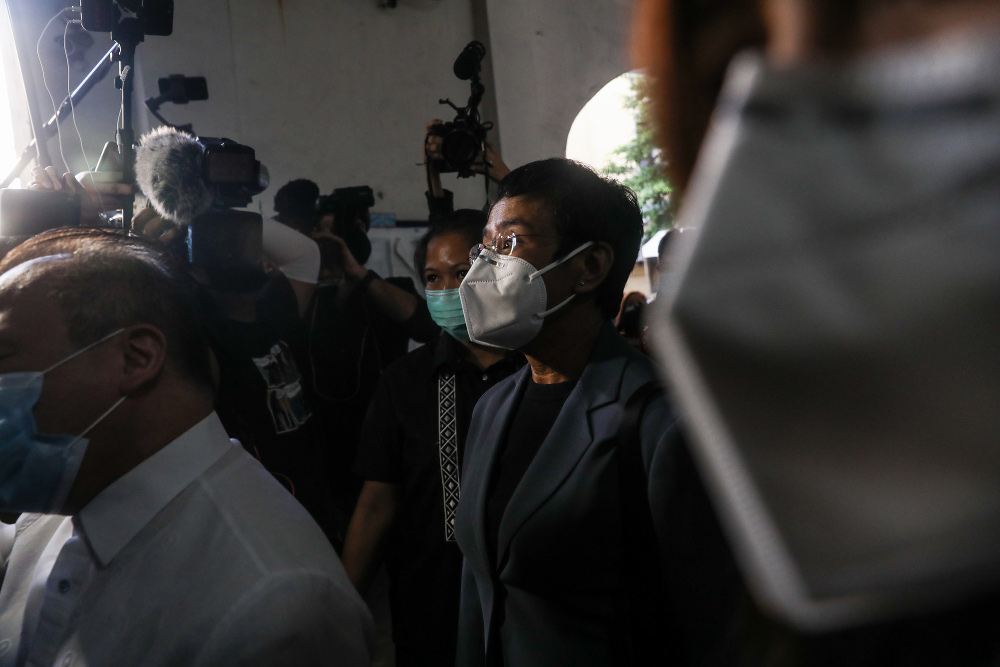 Philippine journalist Maria Ressa (wearing a dark jacket, eyeglasses and face mask) leaves a courtroom in Manila after being convicted in a cyber-libel case, June 15, 2020. [Basilio Sepe/BenarNews]