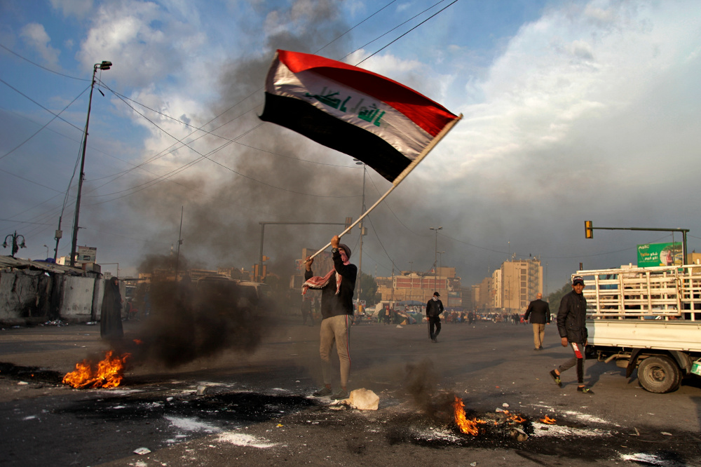 A protester waves the national flag while demonstrators set fire to close streets near Tahrir Square during a demonstration against an Iranian missile strike in Baghdad, Jan. 8, 2020. [AP]