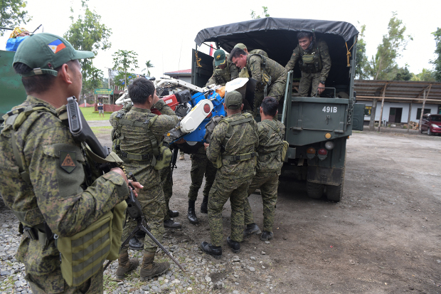Philippine government troops load a small tractor onto a truck in the town of Butig, southern Philippines, July 28, 2019. [Froilan Gallardo/BenarNews]