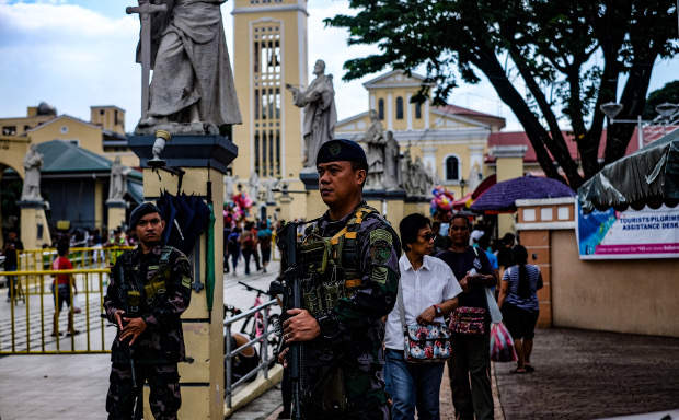 Government security personnel guard an entrance to the Our Lady of Manaoag Church in Manaoag, Philippines Aug 11, 2019. [Jojo Rinoza/BenarNews]