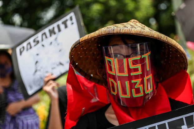 "A protester posted an ""oust Duterte"" message on his face shield during a rally at the University of the Philippines in Manila, July 27, 2020. [Basilio Sepe/BenarNews]"