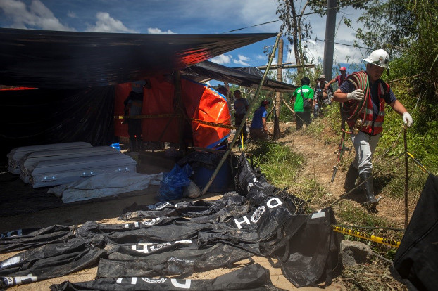 A rescuer walks past body bags and caskets at a command center in Itogon, Philippines, Sept. 19, 2018. [Luis Lawanag/BenarNews]