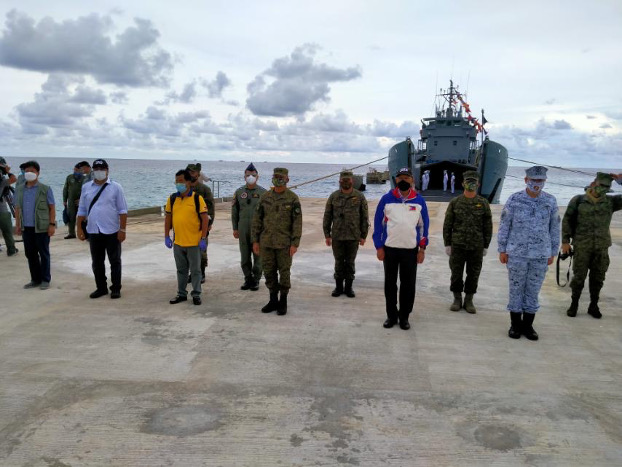 Philippine Defense Secretary Delfin Lorenzana (in white and blue jacket) joins defense officials as he inaugurates a beaching ramp on Pag-asa (Thitu) Island in the South China Sea, June 9, 2020. (Handout Philippine Department of Defense)