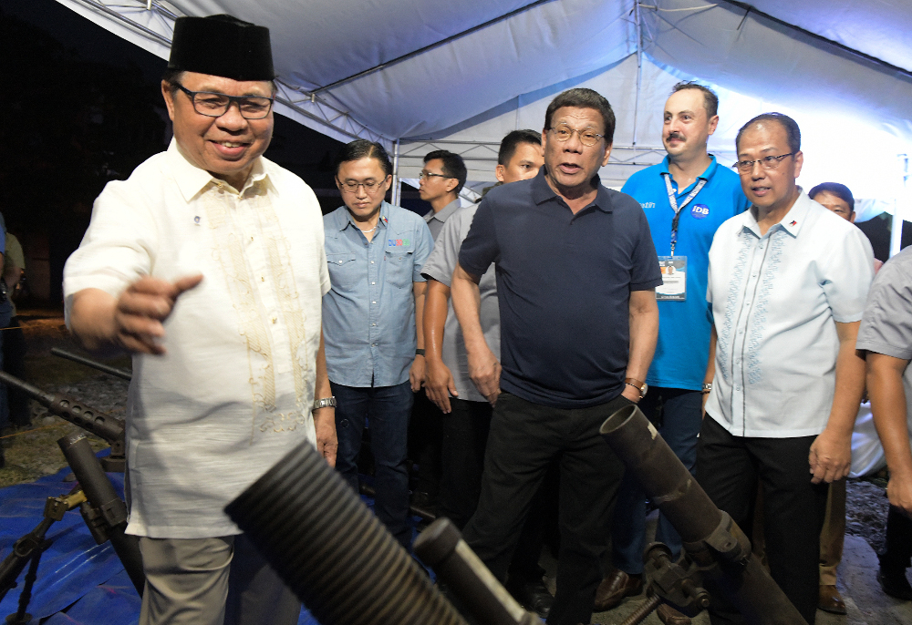 President Rodrigo Duterte (center) joins Moro Islamic Liberation Front leader Ebrahim Murad (left) in inspecting decommissioned firearms in Sultan Kudarat town, southern Philippines, Sept. 7, 2019. [Froilan Gallardo/BenarNews]
