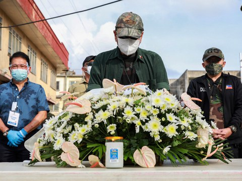 Philippine President Rodrigo Duterte offers flowers and lights candles at the site of a bomb blast in Jolo, Aug. 30, 2020.
