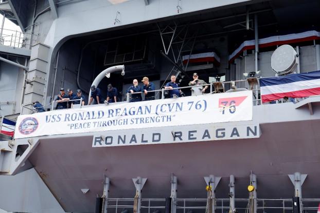 Crew members of the USS Ronald Reagan unfurl a banner on the ship's deck, Aug. 7, 2019. [Jason Gutierrez/BenarNews]