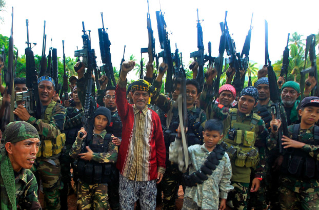 Two boys flank MNLF leader Nur Misuari (center), as they and other guerrillas raise their weapons at a remote camp in Jolo, southern Philippines, May 29, 2016. [Mark Navales/BenarNews]