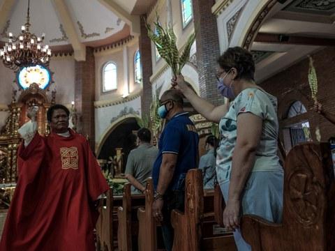 A priest blesses palm fronds as devotees attend Palm Sunday Mass at Santuario De San Juan Evangelista in Dagupan city, Philippines, April 1, 2020.