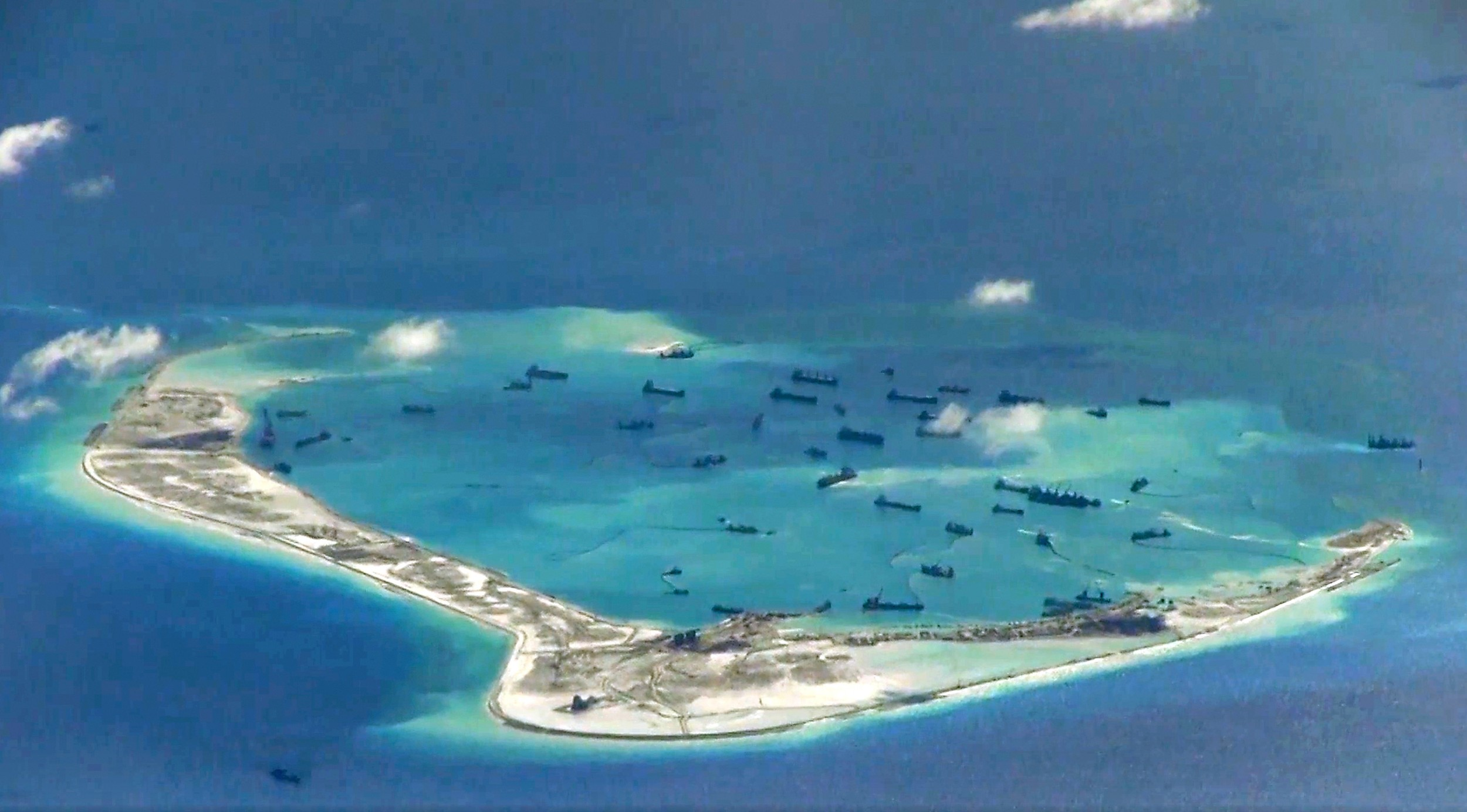 Chinese dredging ships are seen around Mischief Reef in the disputed Spratly Islands in the South China Sea in this image from a U.S. Navy surveillance aircraft, May 21, 2015. (U.S. Navy handout via Reuters)