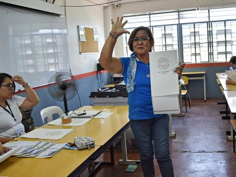 Sen. Leila de Lima, a jailed opposition lawmaker in the Philippines, waves to reporters after voting at a polling precinct in suburban Manila, May 13, 2019.