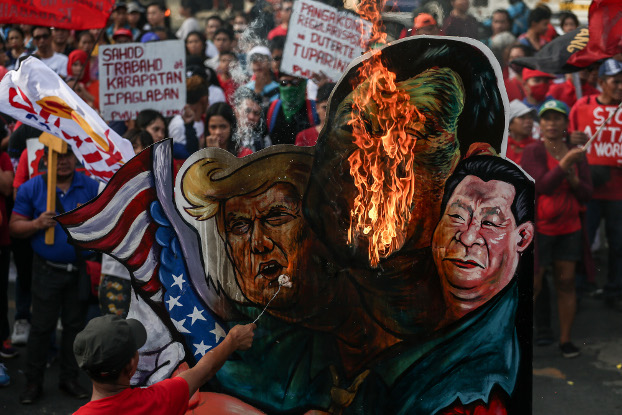 A Philippine activist burns effigies of President Rodrigo Duterte, U.S. President Donald Trump and Chinese President Xi Jinping during a rally in Manila, Nov. 30, 2019. [Basilio Sepe/BenarNews]
