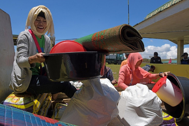 An evacuee sorts out a wash basin and a sleeping mat among relief items distributed by the International Committee of the Red Cross in Marogong, a town in Lanao del Sur province, southern Philippines, March 31, 2019. [Froilan Gallardo/BenarNews]