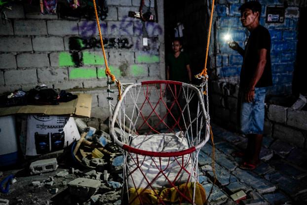 Janine Buan and her neighbor survey damage inside her house in Porac, Pampanga province, following Mnday's earthquake, April 23, 2019. (Jojo Rinoza/BenarNews)