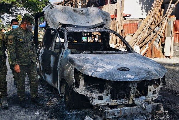 Police officers inspect a squad car burned by Bangsamoro Islamic Freedom Fighters in Datu Piang, southern Philippines, Dec. 4. 2020.