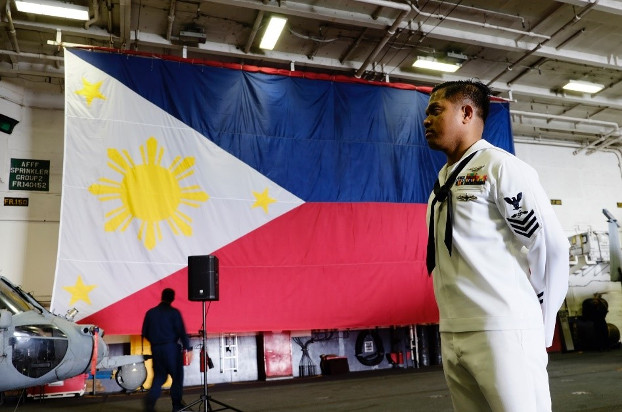 U.S. Navy Petty Officer Fernan Testa stands near a Philippine flag aboard the USS Ronald Reagan after the aircraft carrier dropped anchor in Manila Bay, Aug. 7, 2019. [Jason Gutierrez/BenarNews]