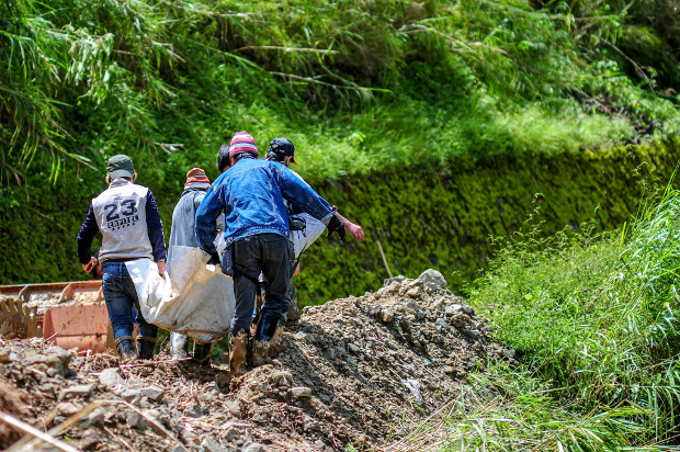 The body of Edwin Banawol, the president of the mining cooperative at Bgy. Ucab who was killed in the landslide, is carried to a command center in Ucab, Itogon after it was recovered by a search team, Sept. 18, 2018.